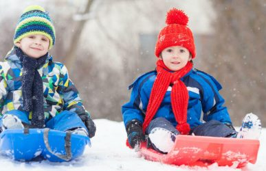 Two boys sledding in snow