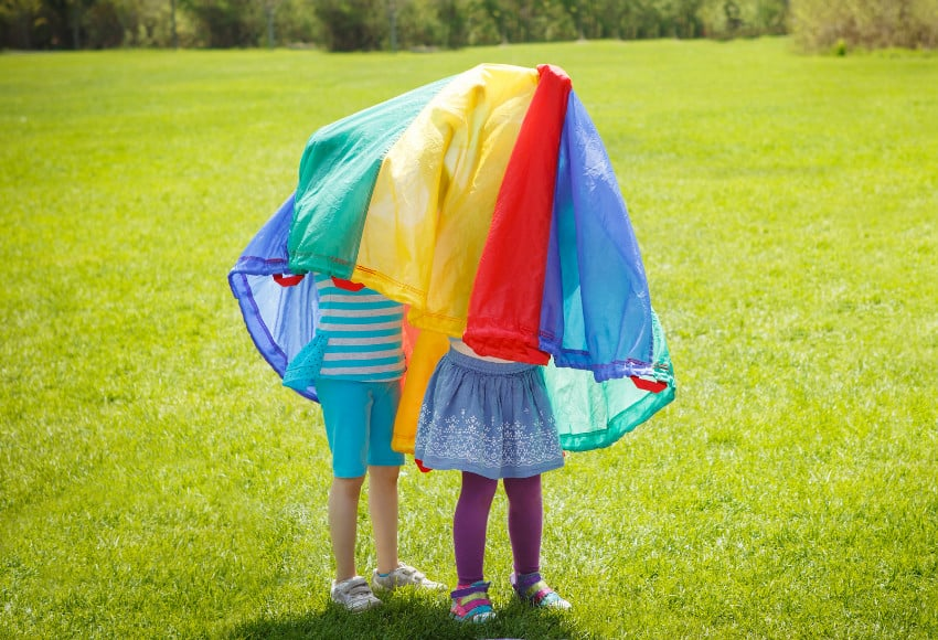 Children under a play parachute