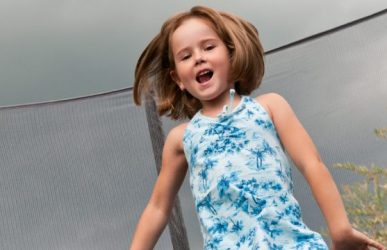 Girl on trampoline with enclosure